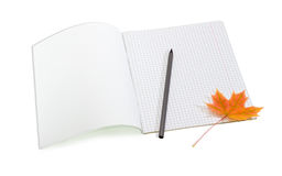 Open school exercise book, pencil and yellowed maple leaf Royalty Free Stock Image