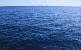Open sea and land on the horizion. Open blue sea and land on the horizon Stock Photos