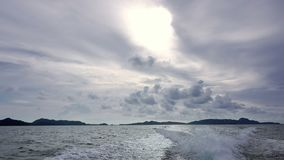 Clouds and Trace Behind the Stern of a Motor Boat. Open sea. The motor boat quickly sails away from the tropical islands. Beautiful clouds in the sky stock video