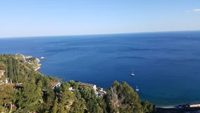 Open sea view in Castelmola. Sea view at Castelmola: the blue of the sea and the green of the surrounding vegetation, and the white of the boat that is crossing Royalty Free Stock Photo