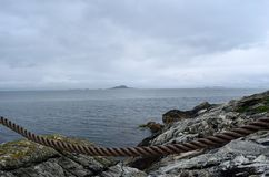 Open sea view on overcast day in the arctic circle with old guard rope Royalty Free Stock Photography