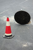 Open sewer manhole. Open manhole of sewer and warning tubes royalty free stock photography