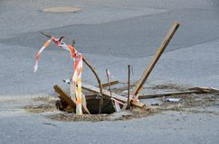 Open sewer well on the roadway. In sunny day stock image