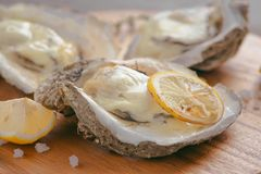 Open shell oyster with lemon and salt on a wooden board.  Stock Photography