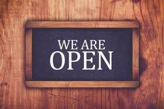 We are open shop message board. Retro toned chalkboard rustic oak wood store door Stock Photography