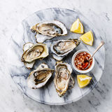 Open shucked Oysters with lemon and spicy sauce. On white marble background royalty free stock photo