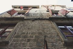 Open shutters of windows on an old stone wall. Bottom view. Building with clothesline outside the home wood window. Architecture, street, city, exterior, house stock photography