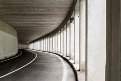Open sided road tunnel. Curving, open-sided road tunnel with spaced cement columns and asphalt road surface Royalty Free Stock Image