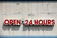 Open sign. Open 24 hours sign on the grunge cement wall stock photo