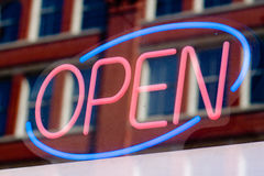 Open sign. A neon sign declares Open! in red and blue in a downtown office window Stock Photos