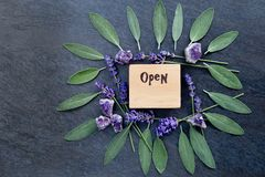 Open sign for alternative therapy business - word burnt in wood with purple lavender flowers, gren sage herb leaves and amethyst. Clusters on gray / grey slate royalty free stock photography