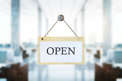 Open sign on blurry office background. Wooden board with open text hanging on blurry office interior background. Work concept. 3D Rendering Stock Photo