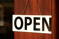 Open sign broad hanging on wooden door in street cafe. Stock Image
