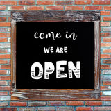 Open sign on  chalk board over brick wall background Royalty Free Stock Image