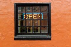 Open Sign in Window with Orange Wall. OPEN neon sign inside black framed window set in orange wall Stock Photos