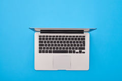 Open silver laptop lying on the blue flatlay Royalty Free Stock Photography