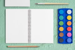 Open Sketchbook and watercolor Watercolor paint palette on Green concrete table. With copy space.Back to school concept royalty free stock image
