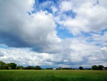 Open skies. Big sky country view with white clouds on blue sky with white house and black roof in the far distance surrounded by meadow and trees Royalty Free Stock Images