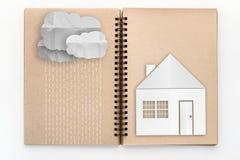 Open skissar boken med molnet med regn, och huspapper klippte techni Arkivfoto