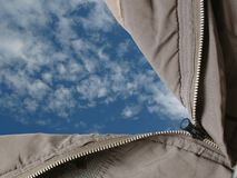 Open sky. A parka with its zipper opened to a sky with cirrocumulus clouds Royalty Free Stock Photography