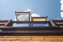 Open skylights mansard windows in wooden house with tile against blue sky. Royalty Free Stock Photo