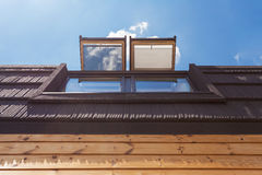 Open skylights mansard windows in wooden house with tile against blue sky. Stock Image
