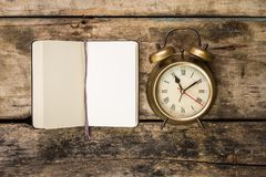 Open small notebook and old-fashioned alarm clock Stock Photos