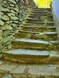 Open small steps at old building, old worn out stony steps behind house. Stony wall from raw boulders. And concrete stock photo