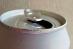 Open soda can rim. Rim of an opened soda can. Condensation on the pinkish aluminium rim. Focus on near rim, background of soft wood wall out of focus Stock Photos