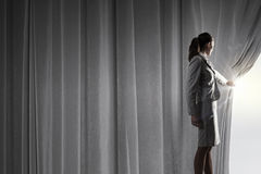 Open something new. Businesswoman opening curtain to new ways and opportunities Stock Photos
