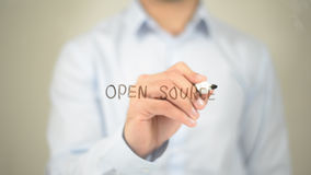 Open Source , Man writing on transparent screen. High quality Stock Photography