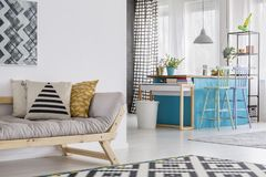 Open apartment with beige couch. Open space apartment interior with beige couch, black and white carpet and blue kitchen island in the background Stock Image
