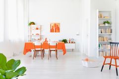 White and orange colored living room interior in modern home. Open space area of white and orange colored living room interior in modern home royalty free stock image