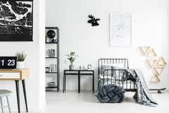 Black stools next to bed. Open space bedroom interior with metal stools next to the bed with black frame and gray bedsheets Stock Photos