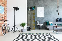 Open space with industrial wardrobe. Scandinavian style carpet in open space interior with lamp, bike and industrial wardrobe royalty free stock images