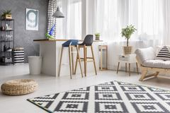 Dining area with white bin. Open space living room interior with geometric carpet and dining area with barstools and white bin stock photo