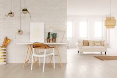 Open space living room interior in real photo with white sofa with cushions in the background, desk with poster and plants standin stock image