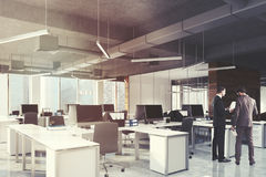 Open space office and meeting room side, toned. Side view of an open space office environment with dark wooden, white and glass walls, rows of white computer Royalty Free Stock Photo