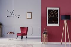Armchair and coffee table. Open space sitting room interior with red armchair, copper coffee table, wooden lamp and painting on the wall Royalty Free Stock Images