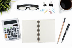 Open spiral blank notebook and calculator on white desk table stock images