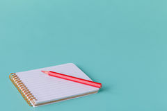 Open spiral blank notebook with pencil on aquamarine desk background Royalty Free Stock Image