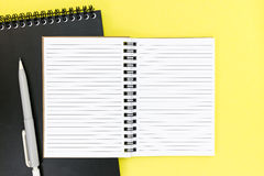 Open spiral notebook, black notepad and mechanical pencil on yel Stock Image