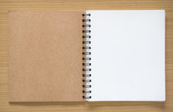 Open spiral notebook. On wood background Stock Photos