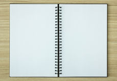 Open spiral notebook. On wood background Royalty Free Stock Images