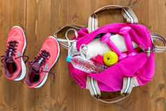 open sports bag and pink running shoes on a wooden floor Stock Images