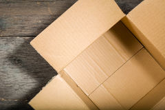 Open square cardboard box on the background of the old wooden table. Royalty Free Stock Images