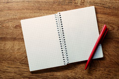 Open square ruled notebook and pen. Open blank white square ruled spiral bound notebook with copyspace and a red ballpoint pen lying on a wooden desk, view from Royalty Free Stock Photo