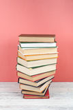 Open stacking book, hardback colorful books on wooden table, red, pink background. Back to school. Copy space for text. Open book, hardback colorful books on royalty free stock photography