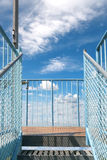 Open stairs to a viewing platform. The last steps of an open staircase to a viewing platform made of metal with a view in the blue and white sky Stock Images