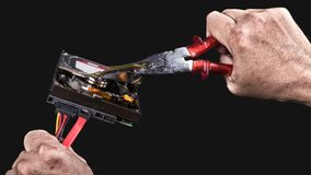 Hard disk drive and pliers in human hands on black background. Open storage device with sensitive personal informations. Data protection or deletion concept royalty free stock image